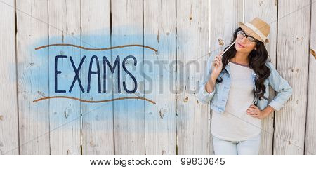 The word exams against pretty brunette thinking and smiling
