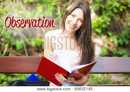 The word observation against pretty student studying outside on campus
