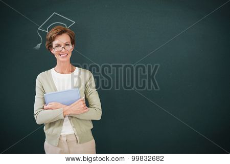Teacher holding tablet pc at library against teal