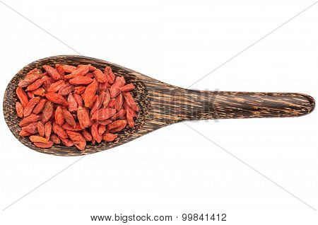 dried goji berries on a wooden spoon isolated on white - superfood concept