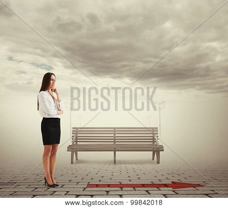 outdoors photo of pensive businesswoman looking at arrow on the floor