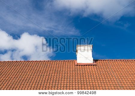 Typical Tiled Roof And White Chimney Against Blue Sky