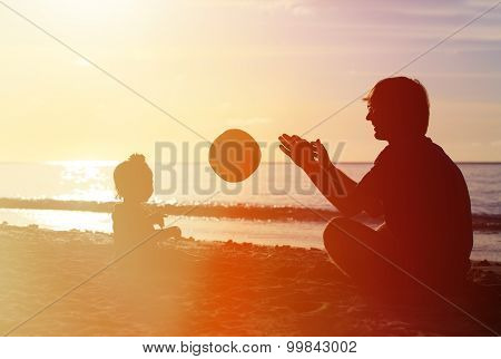 silhouette of father and little daugther play ball
