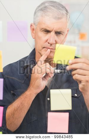 Casual businessman writing on post its stuck on the wall at office