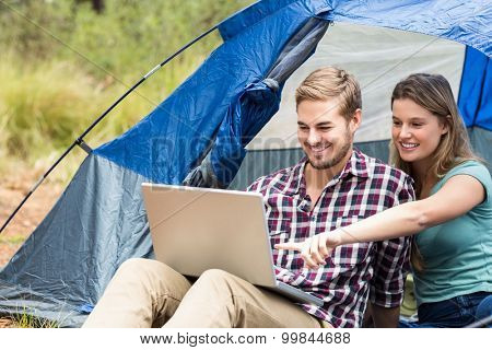 Young pretty hiker couple sitting in a tent looking at laptop in the nature