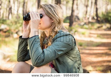 Blonde hiker sitting and looking through binoculars in the nature