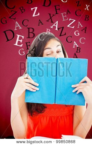 Portrait of a student winking behind a blue book against red background