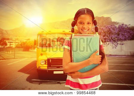 Cute pupil smiling at camera in library against yellow school bus waiting for pupils