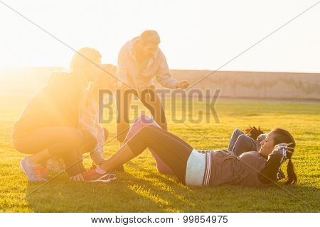 Sporty women doing sit ups during fitness class in parkland