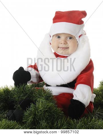 An adorable baby Santa happily siting surrounded by green garland.  On a white background.
