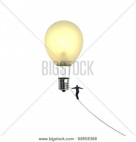 Businessman Walking Tightrope Toward Lightbulb Shape Hot Air Balloon