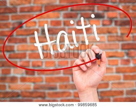Man Hand writing Haiti with black marker on visual screen.