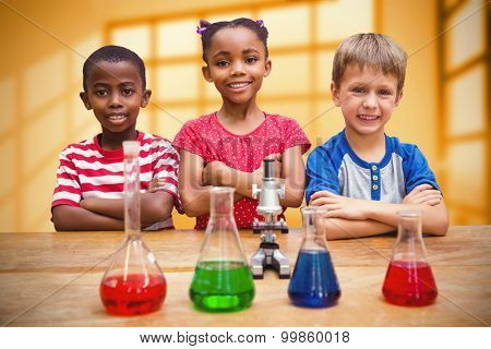 Cute pupils standing with arms crossed behind beaker against room with large windows showing city