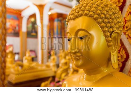 Close up on a traditional Buddha face of a golden statue in the Wat Chalong temple, Phuket, Thailand