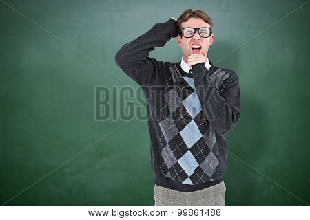 Geeky hipster frowning at camera against green chalkboard