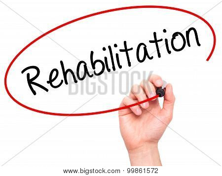 Man Hand writing Rehabilitation with black marker on visual screen.