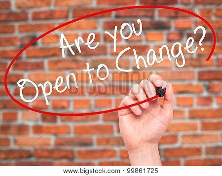 Man Hand writing Are you Open to Change? with black marker on visual screen.