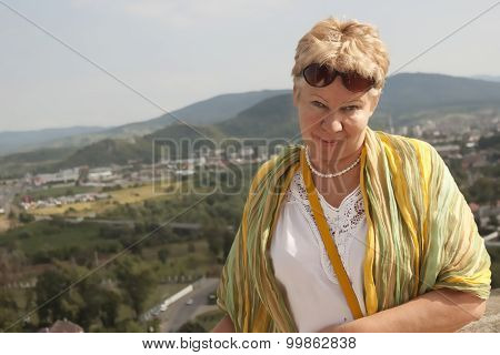Portrait Of A Middle-aged Woman On The Background Of The City And Low Mountains