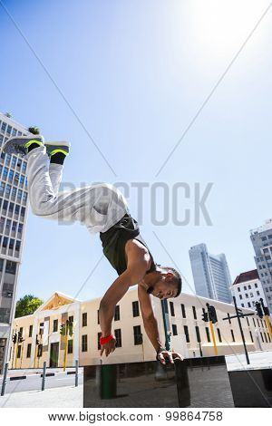 Handsome athlete doing a headstand on a sunny day
