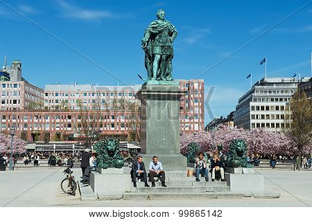 People enjoy lunchtime sitting under KARL XII statue at Kungstradgarden in Stockholm, Sweden.