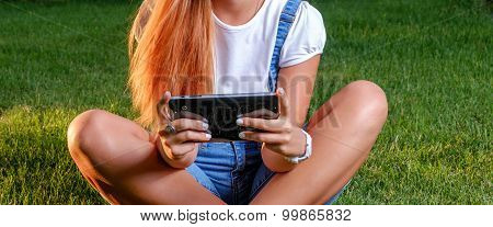 Teenage Girl with tablet computer outdoors cross legged. Young woman is using tablet pc outdoor sitt