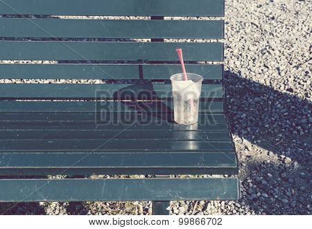 drinks cup with straw lying on bench.