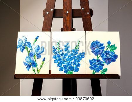 3 paintings of blue flowers on a dark wooden easel