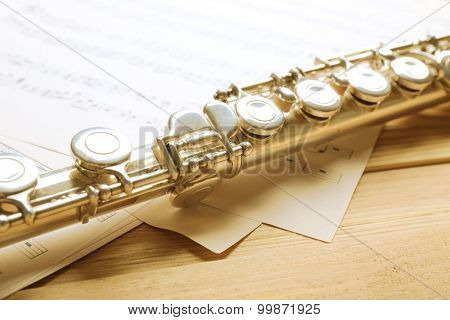 Silver flute with music notes on wooden table close up