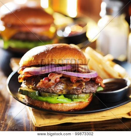 thick bacon cheeseburgers at restaurant with fries