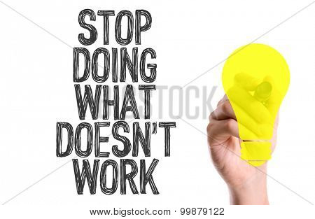 Hand with marker writing the word Stop Doing What Doesn't Work