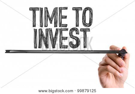 Hand with marker writing the word Time to Invest