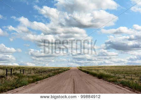A dirt road leading into the distance through a Colorado prairie with a blue cloudy sky.