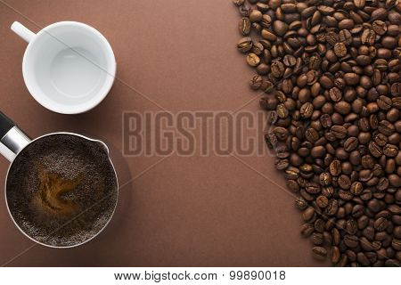Pot of coffee, beans and white empty cup on brown background. Focus on pot