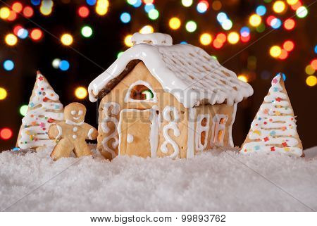 Gingerbread House With Gingerbread Man And Christmas Trees. Gingerbread Man Cookie Standing In Snow