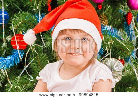Portrait of happy cute little girl in red Santa hat