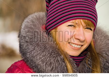 Portrait Of Smiling Girl In Knitted Cap In Wintry Park