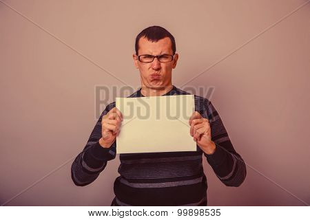 European-looking man of 30 years holding a blank sheet of discon