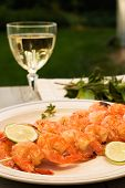 image of chinese food  - grilled shrimps on bamboo sticks served with limes thyme twig and glass of white wine are served outside - JPG