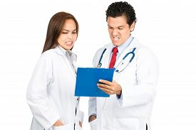 image of horrifying  - A diverse male female hispanic Asian team of doctors reviewing medical charts together grimacing with shocked pained reaction horrified at bad diagnosis - JPG