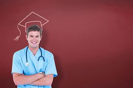 image of tunic  - Young nurse in blue tunic with arms crossed against red background - JPG