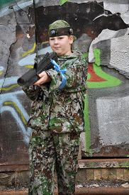 stock photo of paintball  - boy teenager in camouflage and with equipment for paintball - JPG