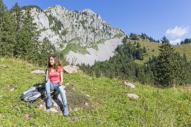 stock photo of thermos  - Young attractive caucasian hiker owman taking a break and drinking refreshment from her thermos in front of a beautiful mountain landscape  - JPG