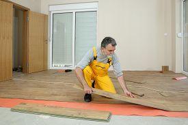 foto of laminate  - Adult male worker installing laminate floor floating wood tile - JPG