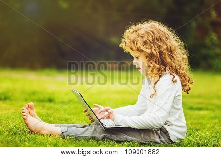 Happy Surprised Child With Laptop Sitting On The Grass.