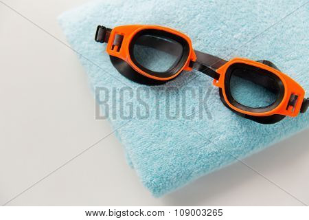 sport, fitness, water sports and objects concept - close up of swimming goggles and towel
