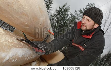 Woodworker Uses Measuring Tool During Building Blockhouse In Winter Forest.