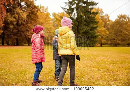childhood, leisure, friendship and people concept - group of happy children in autumn park