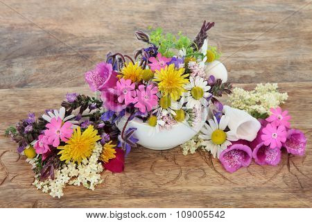 Health care using herbal medicine flower and herb selection in a mortar with pestle over distressed wooden background.