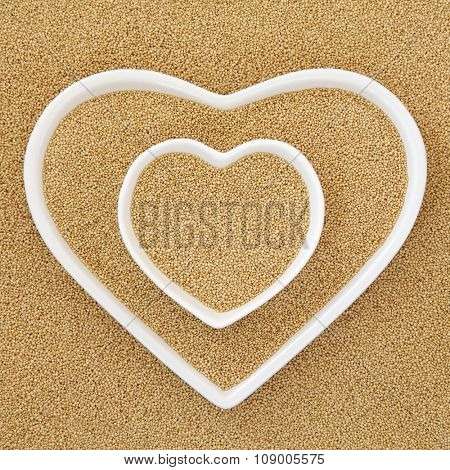 Amaranth grain super food in heart shaped bowls forming an abstract background.