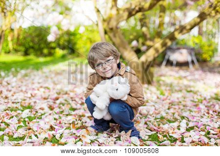 Little kid boy with glasses in spring blooming garden